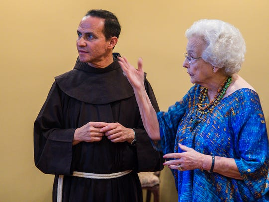 The Rev. Stefano M. Cecchin, OFM, vice postulator of the Friars Minor, discusses a movie trailer with Tilly Chandler, chairwoman of the Lady in Blue Committee, during a reception at Bentwood Country Club August 8, 2017.