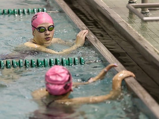 Top, Emily Weiss chats with a teammate between exercises