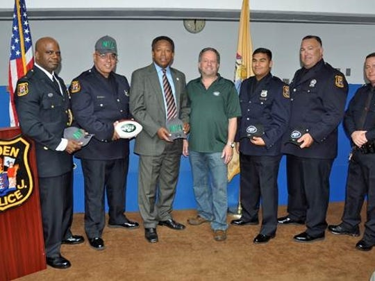 From left: Linden Police Chief Jonathan R. Parham, Officer Angel Padilla, Mayor Derek Armstead, New York Jets Military/Law Enforcement Liaison Representative Steve Castleton, Officer David Guzman, Investigator Mark Kahana and Investigator Peter Hammer get invitations to the Jets' Dec. 5 home game.
