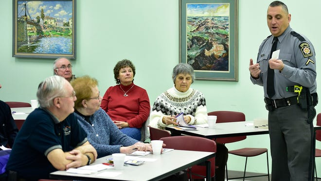 Trooper Ed Asbury, Pennsylvania State Police, talks to a group Wednesday morning, Jan. 27, 2016 at Grove Family Library. The meeting was a part of the Coffee with a Cop program.