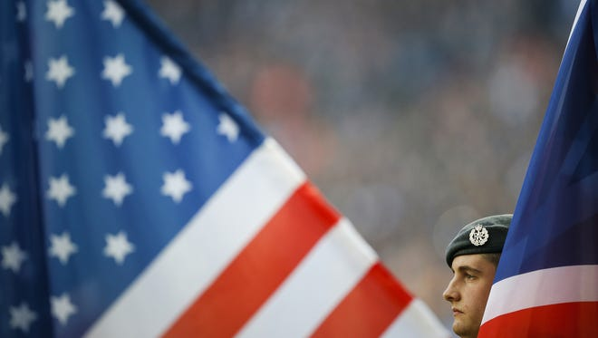 A member of the military holds a flag during the singing of the national anthem during an NFL International Series game at Wembley Stadium in London on Oct. 2, 2016.