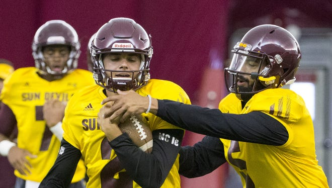 Arizona State Brady White, quarterback, #2, left, tries to keep Manny Wilkins, quarterback, #5, from taking the ball during practice at Verde Dickey Dome in Tempe on August 6, 2016.