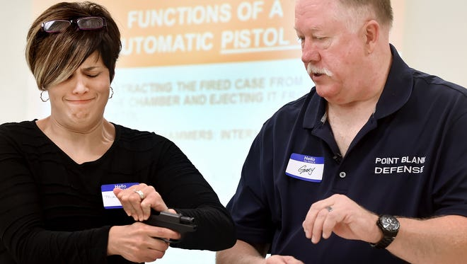 Miriam Hammond discovers the difficulty of racking the slide of a handgun during a training course offered by Gary Smith, owner of Point Blank Defense. Handgun safety is taught by Smith, who is also a local pastor.
