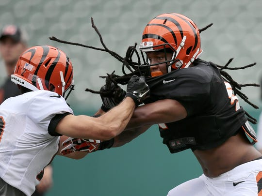 Bengals defensive back Floyd Raven and wide receiver Alex Erickson go head-to-head in drills during training camp on Monday.