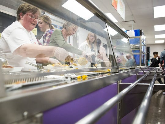 Volunteers work in the kitchen during the annual Thanksgiving Feed My Sheep lunch at Central High School Thursday afternoon.  The event delivered 819 meals to families in need and served several hundred attendees in the school's cafeteria.