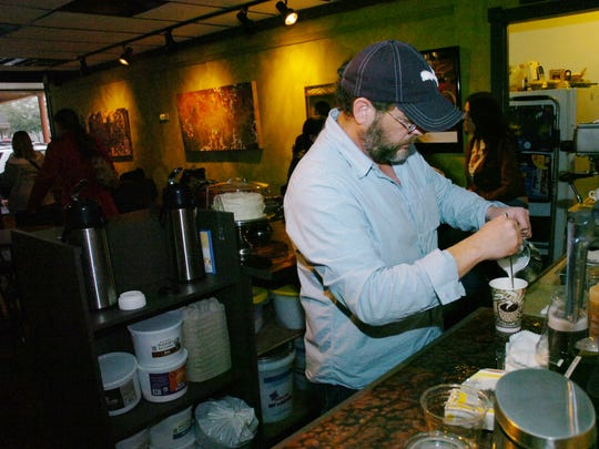 Jeff Phillips, the late owner of Tamp & Grind coffee shop in downtown Alexandria, makes a drink for a customer.