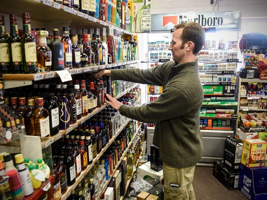 David Vos straightens shelves Monday, Feb. 27, at The Liquor Shoppe on 25th in St. Cloud.