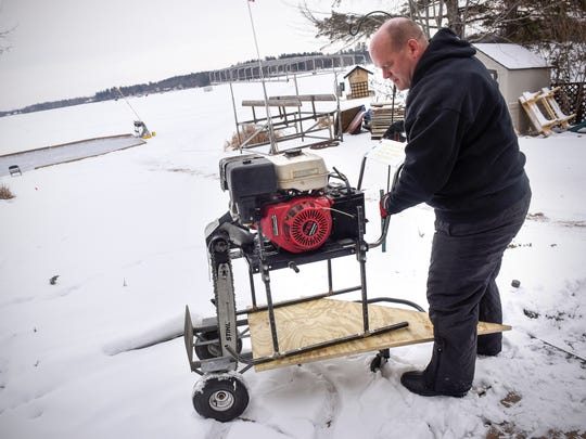Chuck Zwilling moves a custom-made chainsaw rig he and family members will use in an attempt to create the world's largest spinning ice carousel Tuesday, Jan. 2, at Green Prairie Fish Lake near Little Falls.