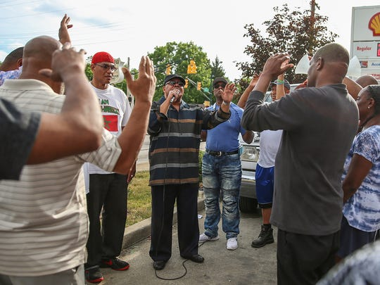 Religious leaders and community members gather in a prayer vigil at the Shell gas station at 34th Street and Sherman Drive, where 50-year-old Sheriff Jallow was fatally shot the previous day, on the east side of Indianapolis, Wednesday, May 30, 2018.