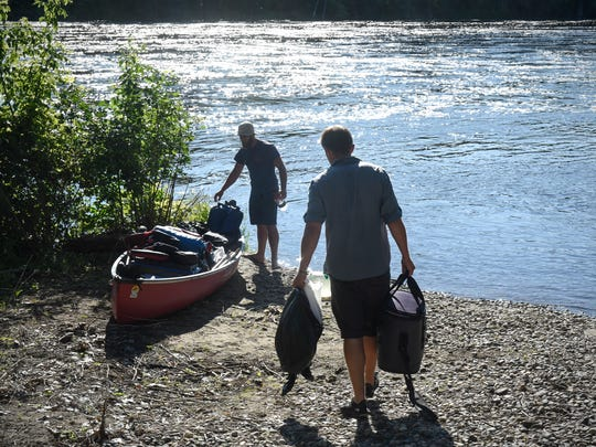 Eric and Daniel Phendler pack their gear into their canoe while preparing to leave the Rotary Park landing Monday, July 16, on the Mississippi River in Sartell.