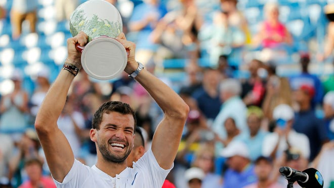 Grigor Dimitrov raises the Rookwood Cup after winning the men's finals match between Nick Kyrgios (AUS) and Grigor Dimitrov (BUL) during the Western & Southern Open at the Lindner Family Tennis Center in Mason, Ohio, on Sunday, Aug. 20, 2017. Dimitrov won his first Masters 1000 match and the Western and Southern Open championship in straight sets, 6-3, 7-5.