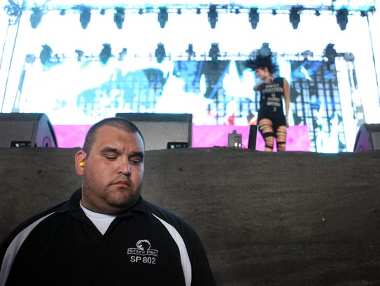 A security personnel stands in the photo pit as Krewella