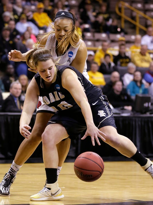 Idaho forward Brooke Reilly grabs a loose ball in front of Louisville guard Antonita Slaughter, rear, during the first half of an NCAA tournament first-round women's college basketball game, Sunday, March 23, 2014, in Iowa City, Iowa. (AP Photo/Charlie Neibergall)