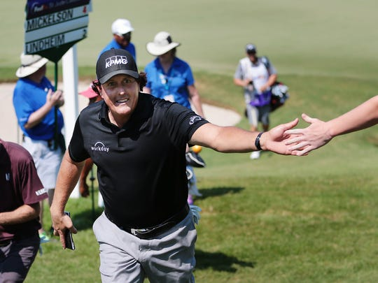 Phil Mickelson gets a high-five after a birdie on the