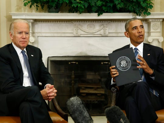 President Barack Obama and Vice President Joe Biden release the Cancer Moonshot Report in the Oval Office of the White House in Washington on October 17, 2016.