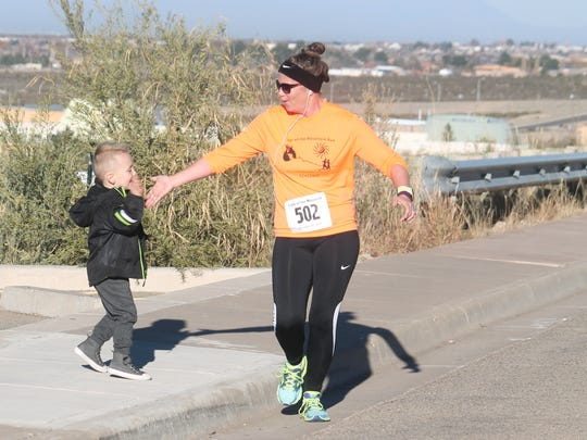 A young boy high-fives a runner from the sidelines on Saturday morning.
