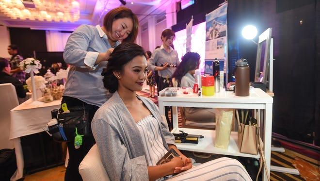 Dareon Rios gets her hair done by Arluis Wedding make-up artist Sadako Fumiyama during the 18th Annual Weddings in Paradise show at the Sheraton Laguna Guam Resort on March 24, 2018.