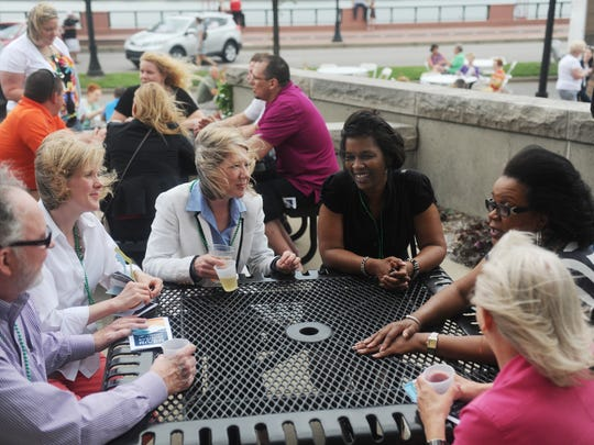"Despite the wind, from left, Phil Hayes, Courtney Hayes, Elizabeth Hayes, Tobi Reeves, Sharon Walker and Susan Vaughn enjoy food an drink on the patio of Old National Bank during a past Evening on the River. Walker and Vaughn have been coming to the event for seven years. ""We love it, we think it might just be our favorite event all year,"" Walker said. ""We find the riverfront so beautiful and peaceful at night."""