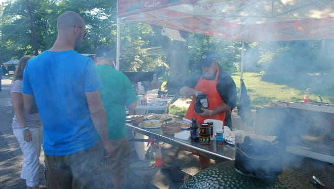 Smoke rises from a pig-roast station at a past Neighborhood Chefs Walk on Alexander Avenue in Chambersburg.