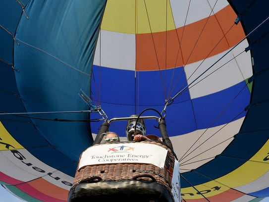 Kynlee Adolph, 9, peers over the edge of a hot air