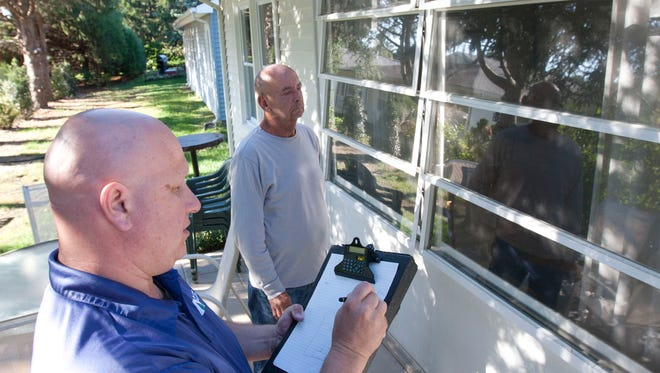 Tim Doerrler(left) energy auditor from New Jersey Natural Gas doing an audit on the home of Anthony Selinski (right), Brick.