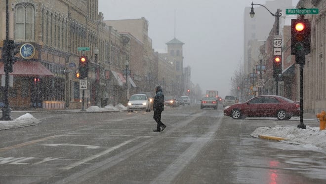 A pedestrian crosses Main Street near Opera House Square Tuesday in Oshkosh as a winter storm hits the city and northeast Wisconsin.