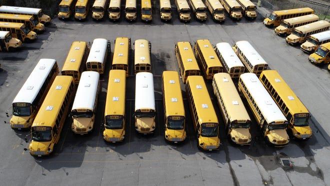 School buses sit unused in a parking lot March 26 in St. Louis.