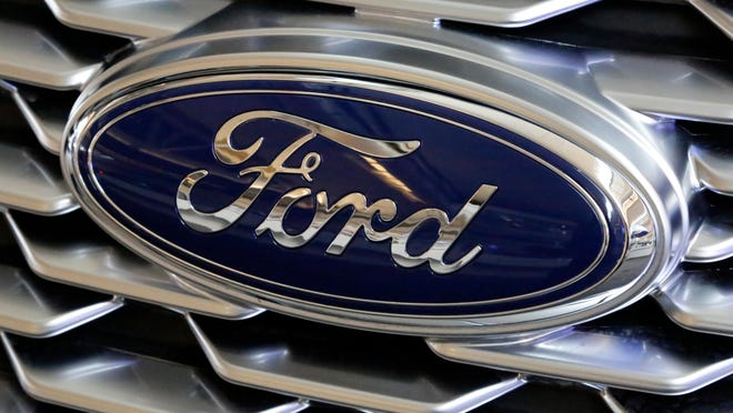 FILE- This Feb. 15, 2018, file photo shows a Ford logo on display at the Pittsburgh Auto Show. Ford is recalling more than 700,000 vehicles in North America because the backup cameras can show distorted images or suddenly go dark. The recall covers most 2020 versions of Ford's F-Series trucks, as well as the 2020 Explorer, Mustang, Transit, Expedition, Escape, Ranger and Edge.  The recall is expected to start Nov. 7, 2020.