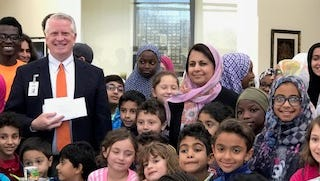 Food Festival - Surrounded by Sunday School students at the Islamic Society of Evansville, Glenn Roberts, Director of the Tri-State Food Bank, accepts donations from Bushra Saqib on behalf of WISE (Women of the Islamic Society of Evansville) as well as the children. Presented items included a check in the amount of $5000 (proceeds from the annual Food Festival), over $300 in cash donations the children collected throughout the year, as well as over 190 pounds of food.