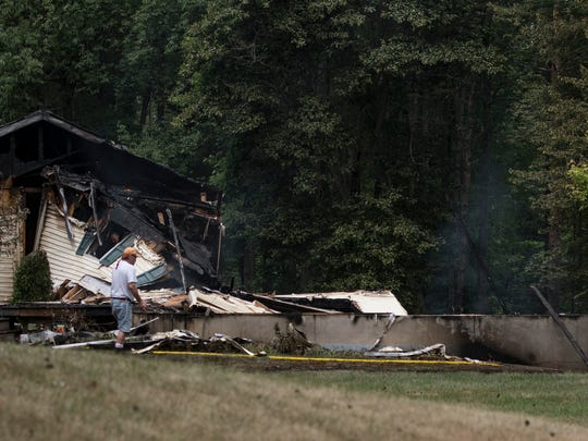 A man looks over the smoldering remains of a home in