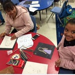 Vicky Garcia (left) and Silvia Garcia enjoy an art activity during a meeting of the Parent and Child Art Club at Broad Street School in Bridgeton.
