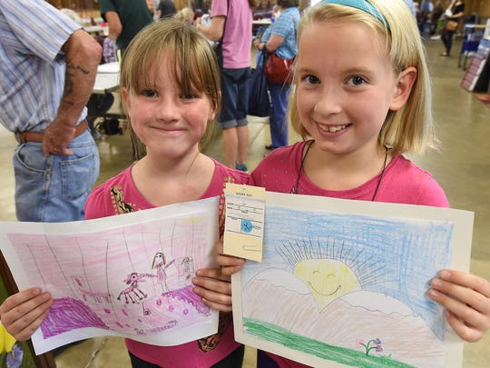 Gemma Demers, 6, left, and Bonnie Demers, 9, show the artwork they entered on Tuesday at the Baxter County Fair.