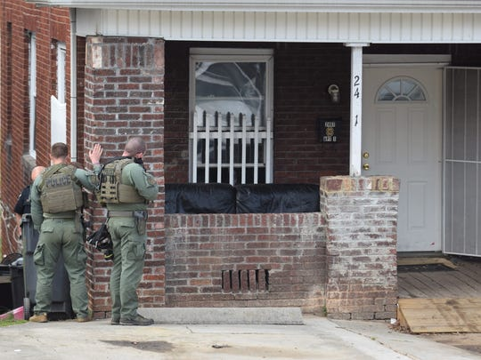 Members of the Knoxville Police Department's Special Operations Squad stand outside a Linden Avenue home where a man refused to come outside after allegedly assaulting his sister on March 13, 2018.