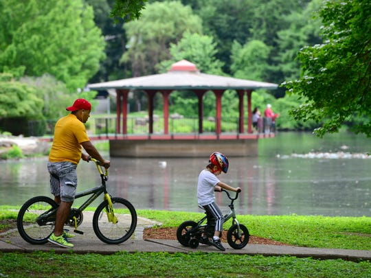 Elias Ortiz, of Bergenfield, and his son, Jason, 5, ride their bikes around Cooper's Pond Park Thursday morning.