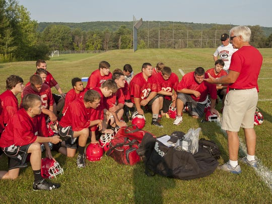 Tom Goddard, the new head football coach at Groton High, talks to his team about the importance of character shortly after 8 a.m. Monday on the first day of practice for high school sports.