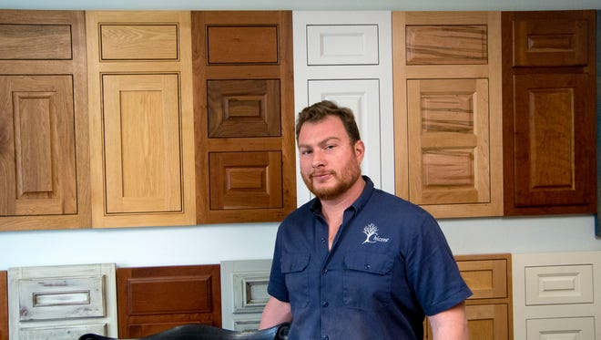 Vincent Chicone shows some of the kitchen cabinet samples he sends to customers to help them decide what they would like to purchase.