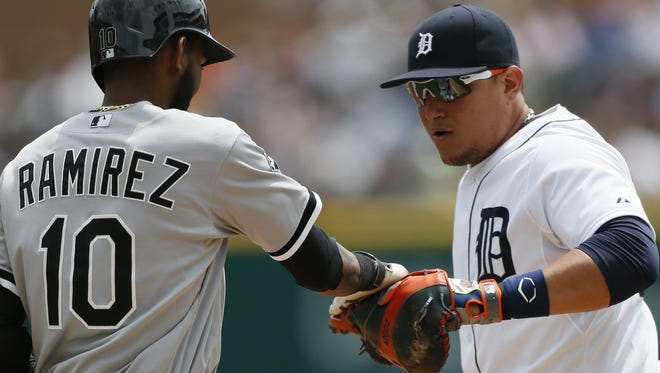 Chicago White Sox baserunner Alexei Ramirez, left, playfully swipes at Detroit Tigers first baseman Miguel Cabrera's glove as he is tagged out July 31, 2014.