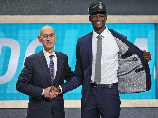 Texas' Mohamed Bamba, right, poses with NBA Commissioner Adam Silver after he was picked sixth overall by the Orlando Magic during the NBA basketball draft in New York, Thursday, June 21, 2018. (AP Photo/Kevin Hagen)