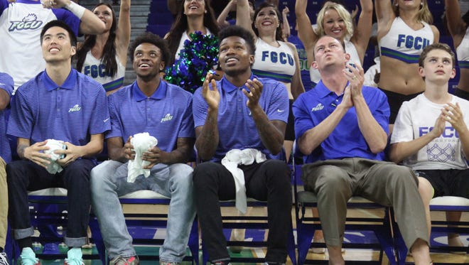 FGCU coach Joe Dooley along with members of the FGCU men's basketball team react after finding out they will play Fairleigh Dickinson in the NCAA tournament on Tuesday in Dayton, Ohio.