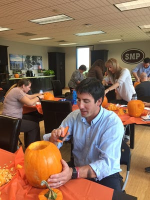 Pumpkins with Purpose: SMP employees Brian Roets, Evyn Grassl and Bonnie Ali and others carve pumpkins to be displayed at The Ronald McDonald House.