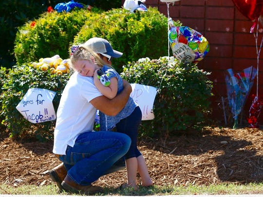 Jason Meredith hugs his daughter Abigail Meredith, 5, at a memorial made for Jacob Hall at Townville Elementary School in Townville Sunday afternoon. Abigail is a student at Townville Elementary school.