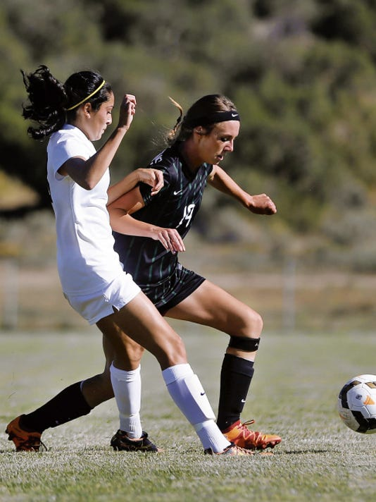 Aztec's Devyn Martinez, left, and Farmington's Hannah Kelley fight for possession of the ball Thursday during a match at the Aztec Tiger Sports Complex.