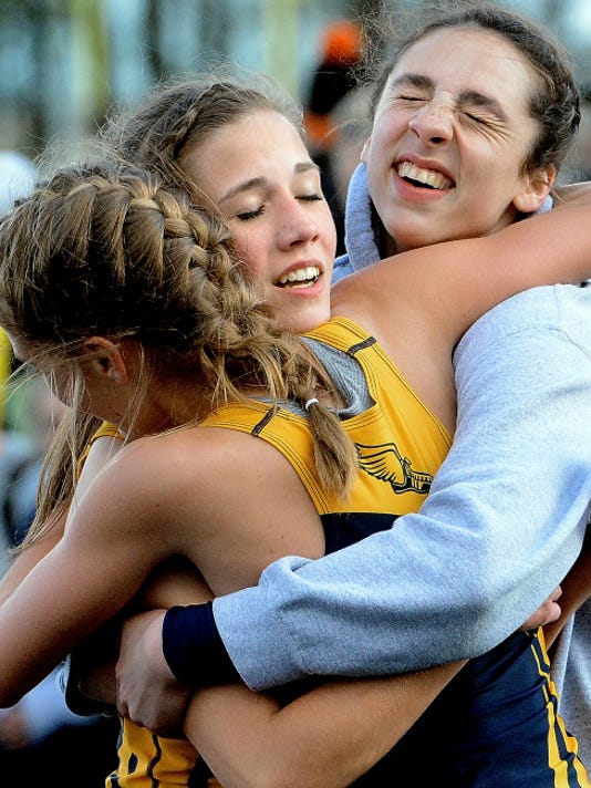 Eastern York's Maddie McLain, left, and Maddie Nalls hug Katie Myer, center, after the 1,600-yard run against visiting York Suburban. McLain won the event and Myer finished third.