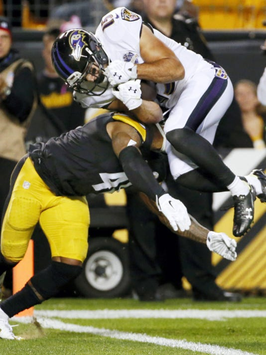 Baltimore Ravens wide receiver Michael Campanaro (15) scores a touchdown over Pittsburgh Steelers cornerback Antwon Blake (41) in the first quarter of an NFL football game, Thursday in Pittsburgh.