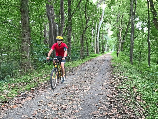 A cyclist rides on the C&O Canal Towpath between Harpers