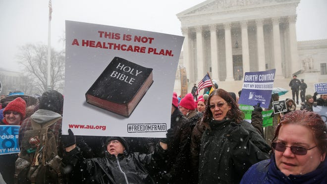 Beth Corbin holds a poster during a demonstration in front of the Supreme Court in Washington, Tuesday, March 25, 2014, as the court heard oral arguments  in the challenges of President Barack Obama's health care law requirement that businesses provide their female employees with health insurance that includes access to contraceptives. Supreme Court justices are weighing whether corporations have religious rights that exempt them from part of the new health care law that requires coverage of birth control for employees at no extra charge. (AP Photo/Charles Dharapak)