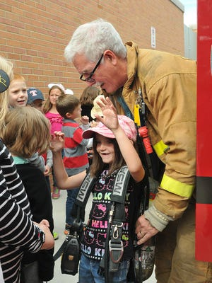 Port Clinton firefighter Bruce Buckingham helps a Bataan Elementary student try on a full-size airpack during safety day at the school on Thursday afternoon.