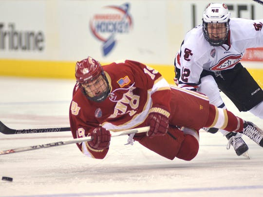 Denver's Troy Terry (19) falls on the ice while battling St. Cloud State's Blake Winiecki (42) for possession during the first period of the NCHC Frozen Faceoff game Friday at Target Center in Minneapolis.