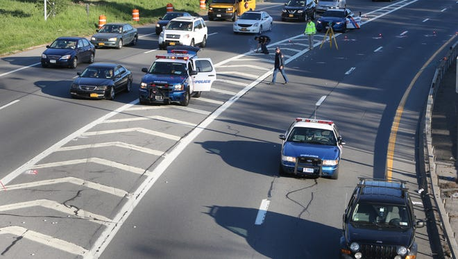Westchester County police conduct an accident investigation on the eastbound Cross County Parkway in Yonkers, after a police officer was struck at an accident scene early May 13, 2015.