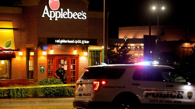 A police offer stands posted at the entrance of an Applebee's restaurant Monday, June 22, 2020, in St. John, Mo., a suburb of St. Louis. A gunman opened fire inside the restaurant, killing one and injuring at least two others, police said.